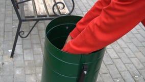 De landloper graaft in de vuilnisbak in het park stock video