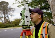De landmeter controleert zijn werk op bouwproject Stock Foto's