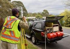 De landmeter controleert zijn werk op bouwproject Stock Foto