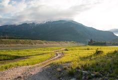 De landweg langs Slangrivier en Centraal Rocky Mountains onder cumulus betrekken hemel in Alpien Wyoming Stock Fotografie