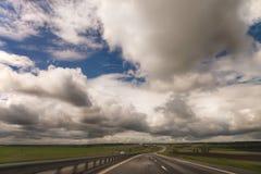De landweg met wolken Stock Afbeelding