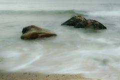De lange blootstelling die van oceaangolven, rond zeewier stromen behandelde keien, Blokeiland, RI stock foto