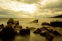 De lange blootstelling van de strandzonsondergang Stock Foto