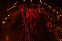 De lange blootstelling van rode auto's steekt en mooie blauwe ziekenwagen in een verkeer op de weg bij nacht aan Stock Afbeelding