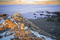 De lange blootstelling van sneeuw en rotsachtig overziet van de oceaan en de kust tijdens de winter stock foto's