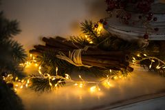 De lange die stokken van kaneel met een kabel, aangestoken Kerstmisslinger worden gebonden, liggen onder de spartakken stock foto