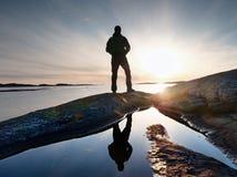 De lange duidelijke zonnige dageraad van het backpackerhorloge over overzees De wandelaarwandelaar geniet van adembenemende zonso stock foto