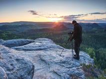De lange fotograaf bereidt camera voor het nemen van beeld van bergen voor stock afbeeldingen