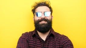 De lange gebaarde mens zet zijn zonnebril vanaf de bovenkant van zijn neus aan stock footage