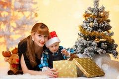 De lange haarvrouw met babyjongen dichtbij de Kerstboom opent een gift Royalty-vrije Stock Afbeeldingen