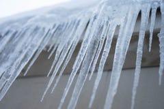 De lange ijskegels bengelen van het dak in de winter stock foto's