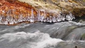 De lange ijskegels hangen boven donker koud water van bergrivier De ijskegels schitteren boven melkachtig water van stroom Takken stock video