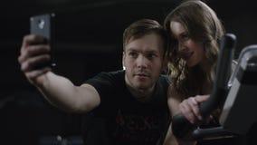 De lange leuke kerel komt aan mooi meisje op hometrainer en toont hoe te om foto beter te maken met haar in de nieuwe gymnastiek stock video