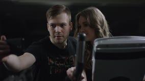 De lange leuke kerel komt aan mooi meisje op hometrainer om foto te maken met haar in de nieuwe gymnastiek stock footage