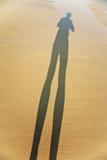 De lange lichaamsschaduw van een mens in het fijne zand van het strand, voeten is Stock Afbeeldingen