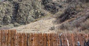 De lange lijn van landelijke houten omheining maakte van dunne houten planken die privé landbouwbedrijf in bergen beschermen Royalty-vrije Stock Foto's