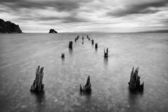 De lange oude houten omvang van de pijlerbrug van strand aan overzees Diepe bewolkte hemel na het grote onweer Verwachting aan su stock afbeelding