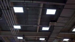De lange pijpen van hvacsysteem en de lampen hangen op plafond van grote wandelgalerij stock video
