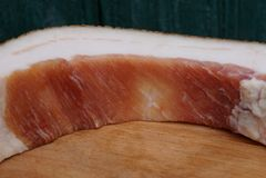 De lange plak van vers varkensvleesvet ligt op een bruine houten raad stock afbeelding