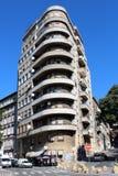 De lange smalle concrete bouw met grote ronde balkons op straathoek royalty-vrije stock afbeelding