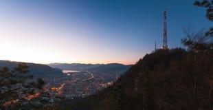 De lange toren van de roostertelecommunicatie boven stad stock foto