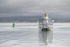 De lange toren van de vuurtorenbouw in zeewater en helder licht onder grijze hemel royalty-vrije stock afbeelding