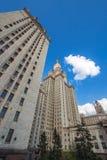 De lange universitaire bouw met pijlen van vensters en gouden spits onder bewolkte blauwe hemel Stock Afbeelding