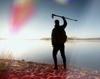 De lange wandelaar in donkere sportkleding met polen en de sportieve rugzak lopen op strand De toerist geniet van zonsopgang Royalty-vrije Stock Afbeelding