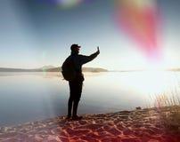 De lange wandelaar in donkere sportkleding met polen en de sportieve rugzak lopen op strand De toerist geniet van zonsopgang Royalty-vrije Stock Foto