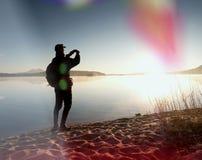 De lange wandelaar in donkere sportkleding met polen en de sportieve rugzak lopen op strand De toerist geniet van zonsopgang Royalty-vrije Stock Foto's