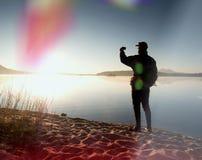 De lange wandelaar in donkere sportkleding met polen en de sportieve rugzak lopen op strand De toerist geniet van zonsopgang Stock Afbeeldingen