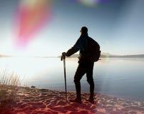 De lange wandelaar in donkere sportkleding met polen en de sportieve rugzak lopen op strand De toerist geniet van zonsopgang Royalty-vrije Stock Fotografie