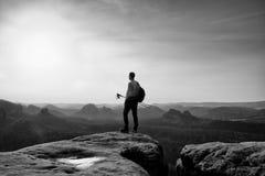 De lange wandelaar van het gemberhaar in grijze t-shirt en donkere trekkingsbroeken op klip Mens met in hand toeristenpolen en sp royalty-vrije stock foto's