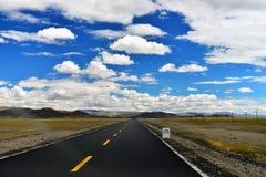 De Lange weg van Tibet vooruit met hoge berg vooraan Stock Foto