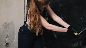 De langharige gouden vrouw schildert de muur met eigenwijsheid In algemeen en bustehouder stock video