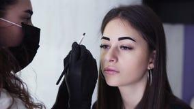 De langharige Kaukasische schoonheidsspecialist in zwart masker past donkere verf op brows van jonge vrouw door bruine kleurstof, stock video