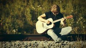 De langharige spelen die van de blondegitarist op de spoorweg op een zonnige dag zitten stock videobeelden