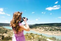 De langharige vrouwelijke toerist in een roze kleding met een camera bevindt zich in de bergen royalty-vrije stock foto's