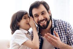 De langharige zoon vertelt geheim in zijn oor van vader stock foto's