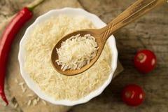 De langkorrelige rijst in een houten lepel op een achtergrond plateert, Spaanse peperpeper, kersentomaat Het gezonde eten, dieet Stock Foto's