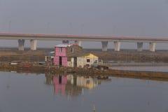 Is de langste brug van de wereld naast de vissenvijver, vijver naast het roze eenvoudige huis Stock Afbeelding