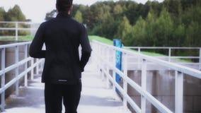 De langzame atleet die van de motie achtermening van jogging genieten Jonge geschiktheidsbus die op dambrug aan stil landelijk la stock footage