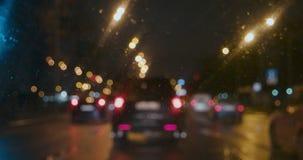 De langzame bewegende auto's met achterlicht in de regen kijken door nat venster stock videobeelden