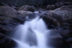 De langzame Fotografie van de Blindsnelheid van een Meeslepende Waterval van Rivierrotsen Stock Fotografie