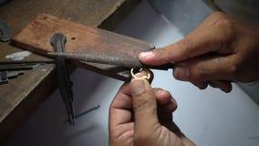De langzame geanimeerde video, goudsmid poetst een gouden of zilveren ring op stock footage