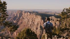 De langzame mens van de motie gelukkige jonge toerist met rugzak wandeling, die van het epische panorama van de de zomerzonsonder stock video
