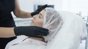 De langzame motie arts zet op beschikbaar GLB op het hoofd van de patiënt vóór kosmetische procedure, behandeling stock video
