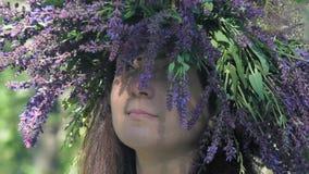 De langzame motie, close-up, mooi meisje met een kroon op een hoofd van de korenbloemen van gebiedsbloemen kijkt omhoog gedacht stock video