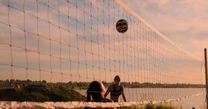 DE LANGZAME MOTIE, LAGE HOEK, SLUIT OMHOOG, ZONgloed: Het atletische volleyball van het meisjes speelstrand springt in de lucht e stock videobeelden