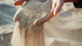 DE LANGZAME MOTIE, SLUIT OMHOOG: Het zand gaat door de vingers van een jonge vrouw over Het zand neemt vingers van a door stock footage